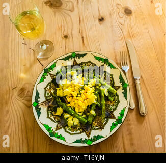 A light lunch of Asparagus Mimosa made with chopped hard-boiled egg and shallots served on a fancy plate on a wooden table - Stock Image