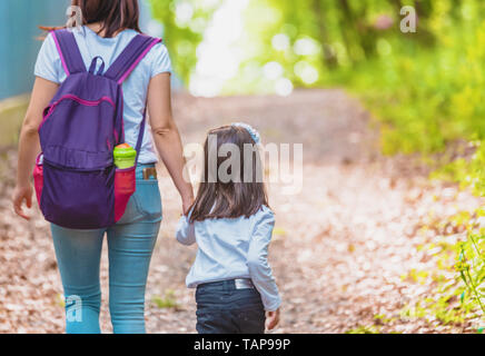 Young mom holds her little girl hand in forest.Happy mother and daughter moments with love and natural emotion.Photo of  mother and daughter having go - Stock Image