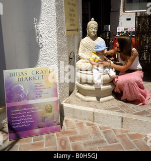Mother and toddler sitting on Buddha statue outside Mijas Craft Market, Mijas Pueblo, Costa del Sol, Andalucia, - Stock Image