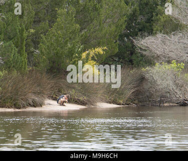 Gone Fishin' Caucasian white male boy fishing in a lake surrounded by trees - Stock Image