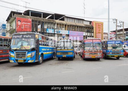 Interurban buses parked at Kanchanaburi central bus terminal, in Thailand. The buses are traditionally very colourful and heavily decorated inside. - Stock Image