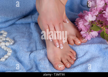 Girl bare feet and hands with french manicure and pedicure in spa salon on blue blue towel with decorative flower and pearls. Spa and recreation - Stock Image