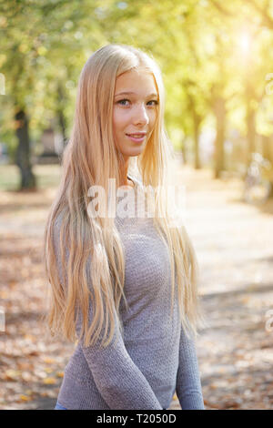 outdoor portrait of blond young woman enjoying sunny day - added sun flare light leak filter - Stock Image
