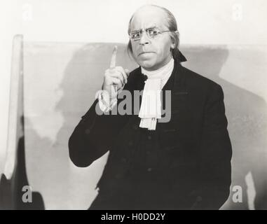 Man in square wire rim glasses making a point - Stock Image