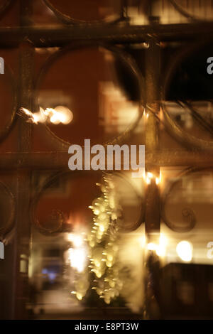 Reflections in a shop window. Swedish city on a icy winter night, blurred. - Stock Image