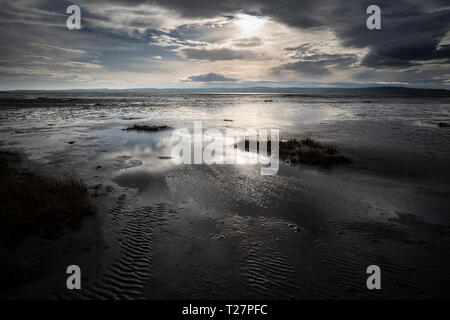 Lindisfarne or Holy Island, Northumberland coast south of Berwick-on-Tweed, England. Tide covers the sands and approaches the causeway. - Stock Image