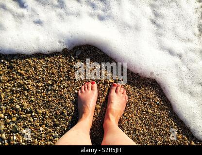 Looking down from above onto a pair of bare feet on a pebble beach with a white wave flowing over in a Summer vacation image - Stock Image