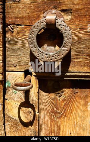 Antique rustic metal key in door lock and metal knocker from an old wood door in Gistaín (Chistau valley, Sobrarbe, Huesca, Aragón, Spain) - Stock Image