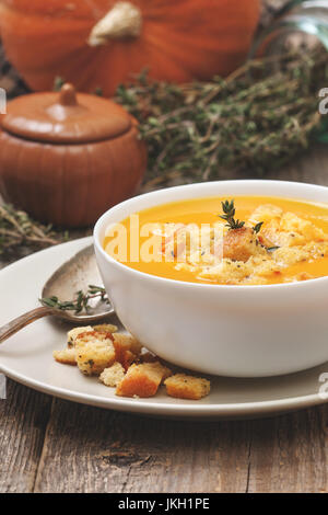pumpkin soup - puree with croutons  in a white bowl on the old wooden background (Toning) - Stock Image