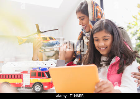 Mother in hijab watching children playing with toys and digital tablet - Stock Image