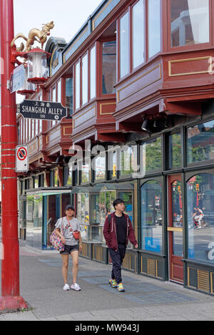 Young Asian couple walking past the historic Sam Kee Building in Chinatown, Vancouver, BC, Canada - Stock Image