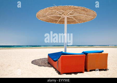 Parasol and sun loungers on the beach - Stock Image