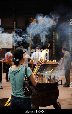Woman praying using incense sticks, temple, Emei Shan (Emei Mountain), China - Stock Image