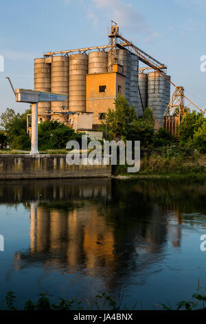 Old factory with silos and reflection on the water - Stock Image
