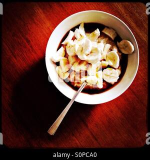 Porridge with banana and maple syrup for breakfast - Stock Image