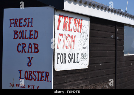 Fisherman's hut advertising fresh fish, crab and lobster for sale on the beach in Suffolk - Stock Image