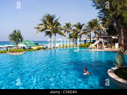 Tropical Hotel swimming pool with swimming child and view towards blue Andaman Sea - Stock Image