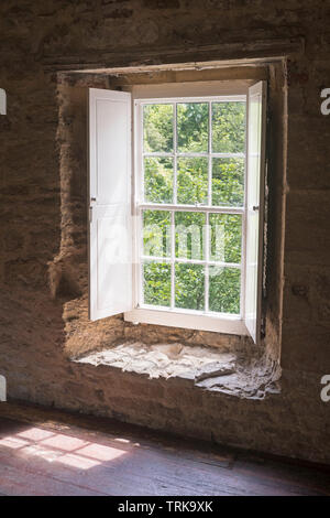 Looking out of a shuttered sash window in Aydon Hall, near Corbridge, Northumberland, England, UK - Stock Image
