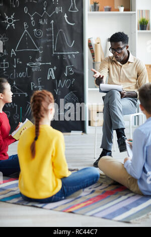 Confident African-american teacher asking one of learners question while explaining one of points of new topic - Stock Image