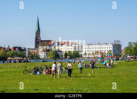 Park at castle Schwerin, people playing on the grass, cathedral in the back, Schwerin, Germany - Stock Image