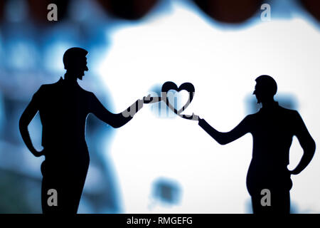 Gay LGBT wedding couple grooms holding hands with love heart shape dancing happy cake topper. - Stock Image
