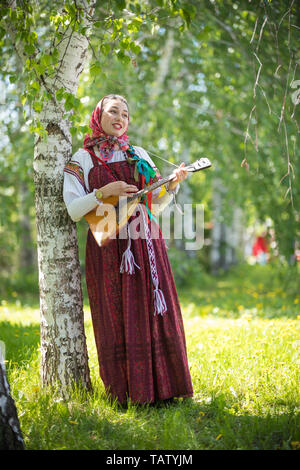Young romantic woman in traditional russian clothes standing in the forest and holding balalaika, vertical - Stock Image