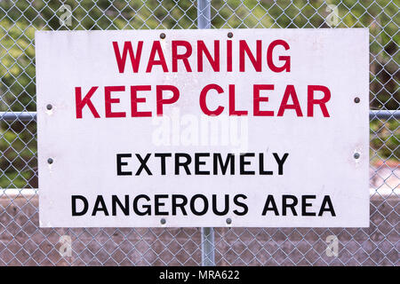 Warning Keep Clear sign on a chain link fence at a hydroelectric dam on the Sacandaga River in the Adirondack Mountains, NY USA - Stock Image