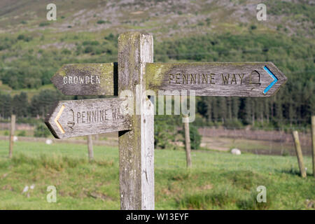 A wooden signpost giving directions along the Pennine Way in Crowden, Derbyshire, England, UK - Stock Image