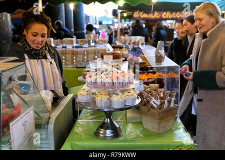 Young woman buying baked goods on a stall with gingerbread men and cupcakes for sale in Borough Market in South London, England UK  KATHY DEWITT - Stock Image