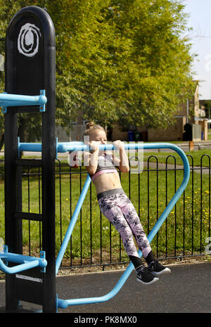 A six year old girl doing 'pull ups', on equipment in a free to use outdoor fitness area - Stock Image