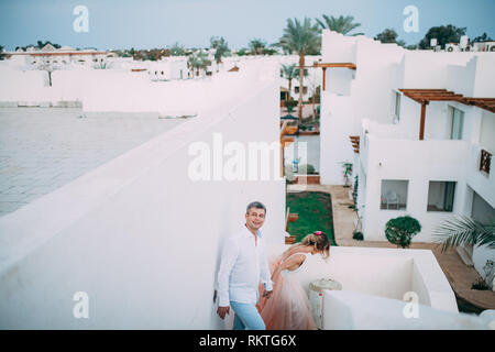 Happy newlyweds walk on terrace of white house against background of palms during the honeymoon in Egypt. - Stock Image