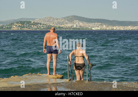 A middle-aged couple prepares to have a swim in the Sea of Marmara on Büyükada, the largest of the Princes - Stock Image