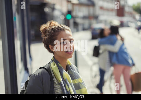 Pensive young woman looking away on sunny urban street - Stock Image