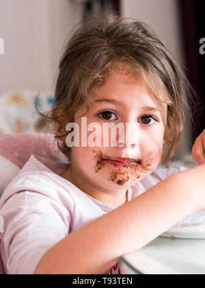 Caucasian girl with chocolate messy face indoors - Stock Image
