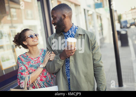 Smiling young couple with coffee walking arm in arm along storefronts - Stock Image