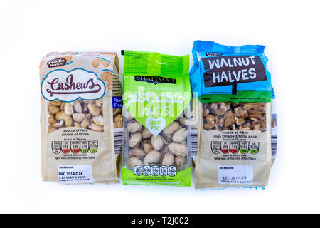 Nuts in cellophane packaging on white background - Stock Image
