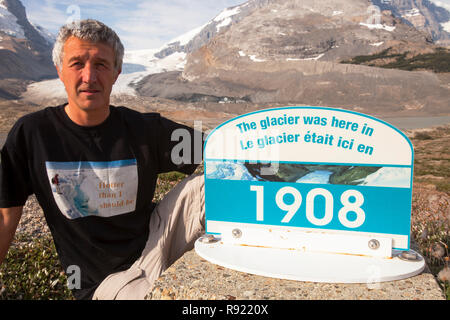 The Athabasca glacier is receding extremely rapidly and has lost over 60% of its ice mass in less than 150 years. A sign marks where the glacier stood in 1908. Ashley Cooper of Global Warming Images makes a protest in the foreground. - Stock Image