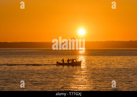 Newlyn, Cornwall, UK. 5th May 2019. UK Weather. With no wind, and calm seas,  this fishing boat headed out to sea from Newlyn harbour  as the sun rose above St Michaels Mount.  Credit Simon Maycock / Alamy Live News. - Stock Image