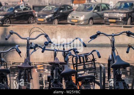Row of bicycles and cars parked alongside opposite sides of a canal, Amsterdam, Netherlands. - Stock Image