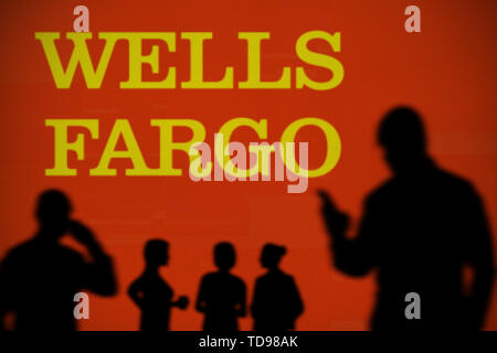 The Wells Fargo logo is seen on an LED screen in the background while a silhouetted person uses a smartphone in the foreground (Editorial use only) - Stock Image