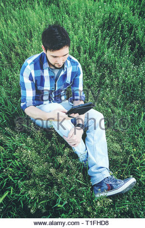 Man reading a ebook alone surrounded by nature - Stock Image