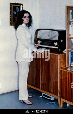 young pretty brunette female wearing a white trouser suit standing next to vintage radio set 1970s hungary - Stock Image