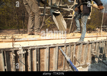 Pouring concrete into the construction of the house. Builders are pouring ready-mixed concrete - Stock Image