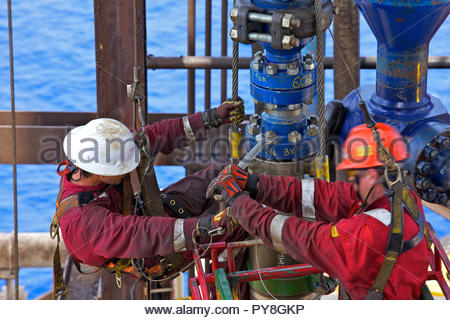 Workers tightening nuts on offshore oil platform - Stock Image