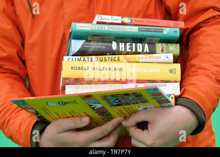 Hay Festival, Hay on Wye, Powys, Wales, UK - Thursday 30th May 2019 - A visitor to the Festival makes his way to the tills in the Festival Bookshop with a stack of books he has chosen to buy at the 32nd Hay Festival. Photo Steven May / Alamy Live News - Stock Image