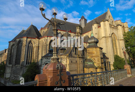 Morning view of the impressive gothic Saint Michael's Church and lamp post of Saint Michel bridge in Ghent. - Stock Image
