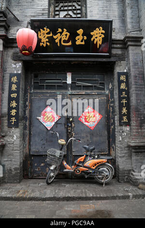 Door of a traditional house in Pingyao, China, with motorbike and Chinese writings - Stock Image