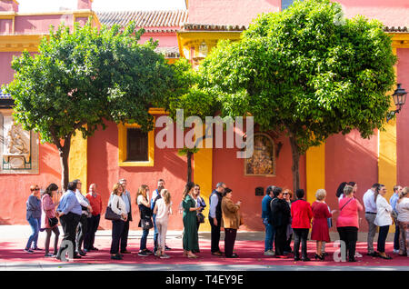 A line of people waiting to get inside a church in Seville - Stock Image