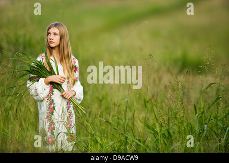 Young girl gathering wild grasses in summer field, wearing traditional Russian costume - Stock Image