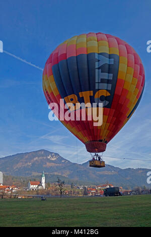 Hot air balloon soars over field and town Ljubno ob Savinji in background. Slovenia. - Stock Image